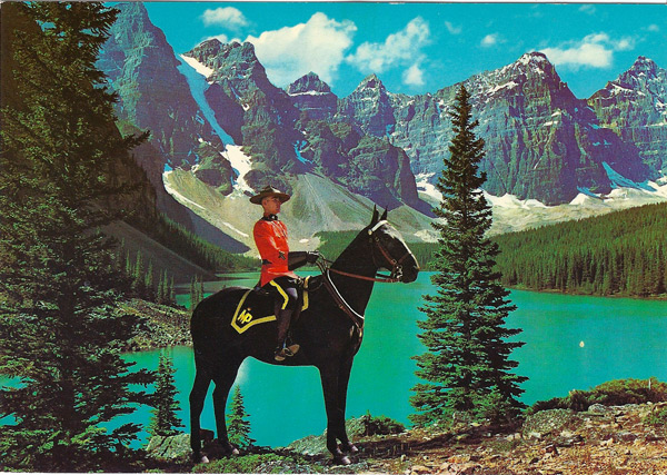 A membr of the famous Royal Canadian Mounted Police set against a majestic mountain background